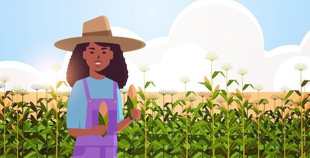 トウモロコシ畑の有機農業の上に立ってのオーバーオールでトウモロコシの穂軸countrywomanを保持している女性農家