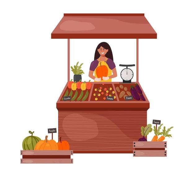 女性農家が市場のカウンターで野菜や果物を売る店員がカボチャを持っている