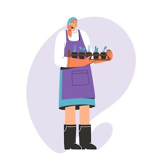 Женщина-фермер стоя и держа коробку с саженцами сельскохозяйственных растений.