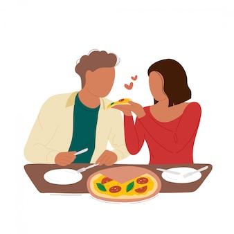 Женщина кормит парня ломтиком пиццы