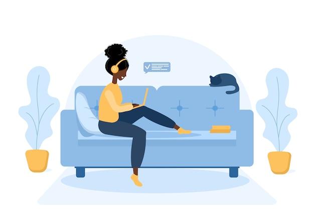 Женщина-фрилансер. африканская девушка в наушниках с ноутбуком, сидя на софе.