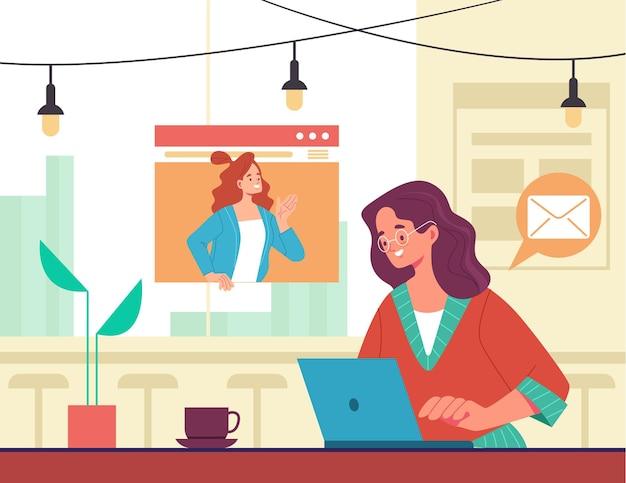 Женщина-фрилансер, сидящая за столиком в кафе и работающая
