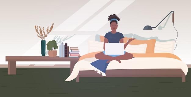 노트북을 사용하여 침대에 앉아 여자 프리랜서 홈 코로나 바이러스 유행성 검역 개념을 유지