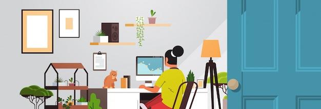 Woman freelancer using computer monitor working at home during coronavirus quarantine freelance