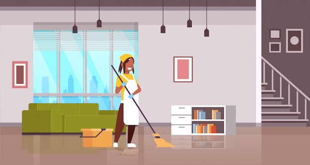 Woman in gloves and apron washing floor   girl using mop housewife doing housework cleaning concept modern apartment living room interior  horizontal full length