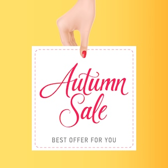 Woman hand holding card with autumn sale lettering