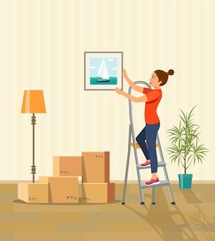 壁に絵をぶら下げている女性。新しい家の引越しボックス。