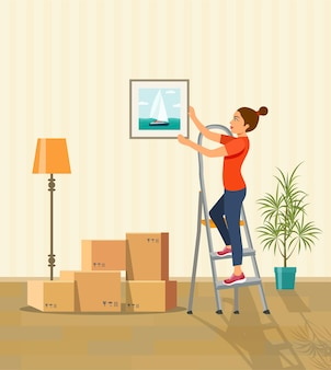 Woman hanging picture on the wall. moving boxes in new house.