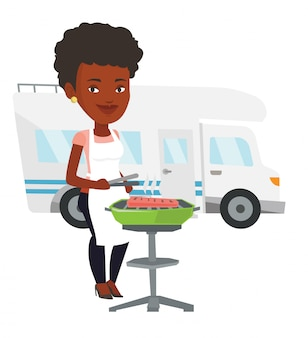 Woman having barbecue in front of camper van.
