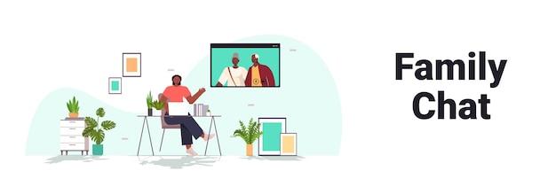 Женщина, имеющая виртуальную встречу со старшими родителями во время видеозвонка, семейный чат, концепция онлайн-общения, интерьер гостиной, горизонтальный