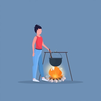 Woman hiker cooking meals girl preparing food in bowler boiling pot at campfire hiking camping concept female traveler on hike full length flat