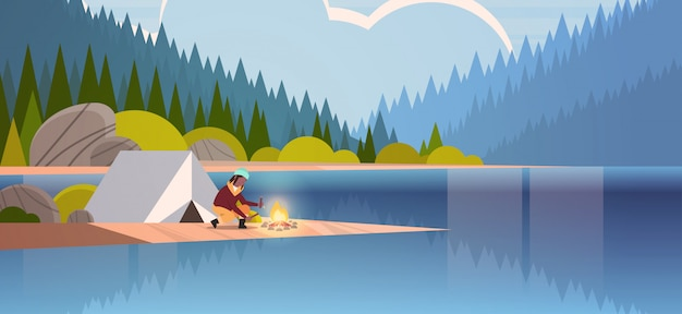 Woman hiker making fire near tent camp   girl holding firewood for bonfire hiking camping concept landscape nature river forest mountains background horizontal full length