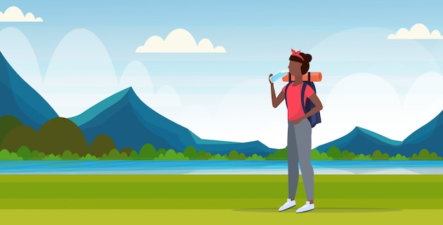 Woman hiker with backpack drinking water african american girl traveler on hike hiking concept mountains landscape background full length flat horizontal