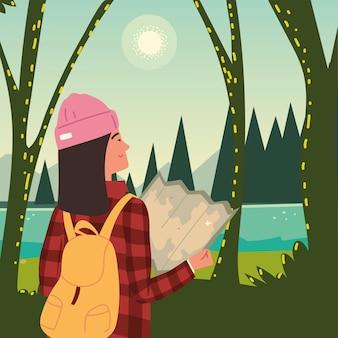 自然の森を探索する地図を持つ女性ハイカー