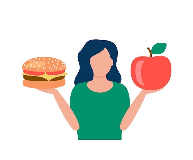 여성은 건강에 좋은 음식과 나쁜 음식 사이에서 햄버거와 사과를 손에 들고 있습니다.