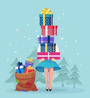 Женщина держит стопку красочных упакованных подарочных коробок