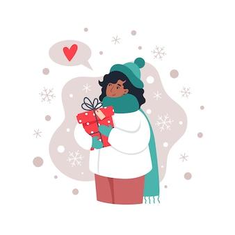 贈り物を持って、手で雪片をキャッチする女性