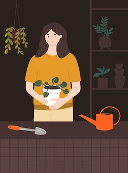 Woman holding big pot with pilea plant home gardener in room with plants stand tools watering can
