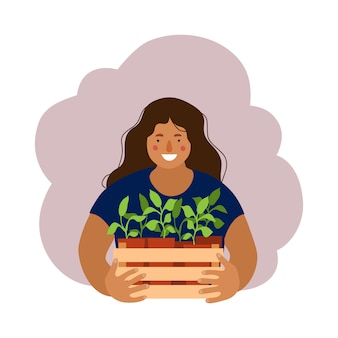 Woman holding a box with garden seedlings.