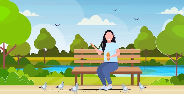 Woman holding bread and feeding flock of pigeon overweight girl sitting wooden bench having fun outdoor public park landscape background flat full length horizontal