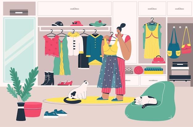 Женщина держит платье у своего гардероба и выбирает наряд