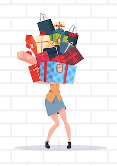 Woman holding gift boxes stack over white brick wall background holiday presents concept
