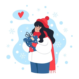 Woman holding a gift and catches snowflakes with her hand