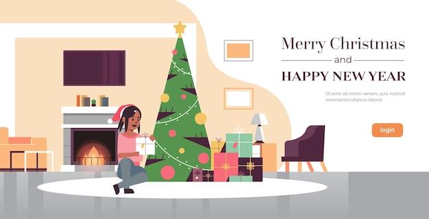 ギフトプレゼントボックスを保持している女性メリークリスマス新年あけましておめでとうございます休日のお祝いのコンセプトモミの木の近くに座っているサンタ帽子の女の子モダンなリビングルームのインテリア全長コピースペース水平ベクトルi