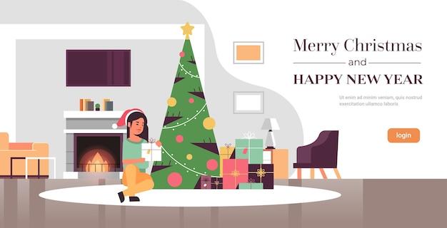 Женщина, держащая подарочную коробку с новым годом, концепция празднования праздника, девушка в шляпе санта-клауса, сидящая возле елки, современный интерьер гостиной, полная длина, копия пространства, горизонтальный вектор, i