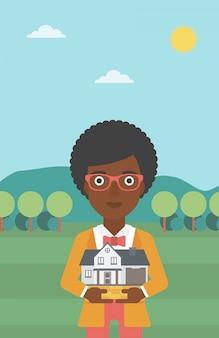 Woman holding house model vector illustration.