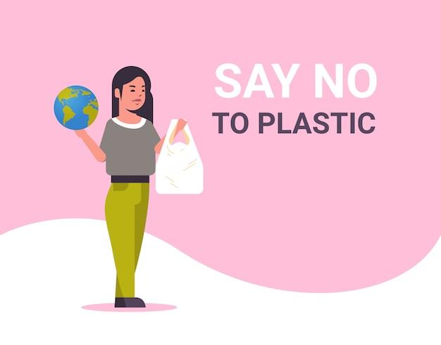 惑星とポリエチレンのバッグを保持している女性は、プラスチックの汚染リサイクルの生態学の問題は地球の概念を保存しないと言う女性エコ活動家全長フラット水平