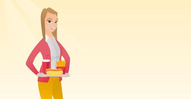 Женщина держит поднос полный фаст-фуд.