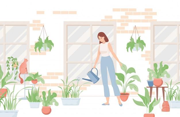 水まき缶を保持し、家の近くや部屋で家の植物に水をまく女性。