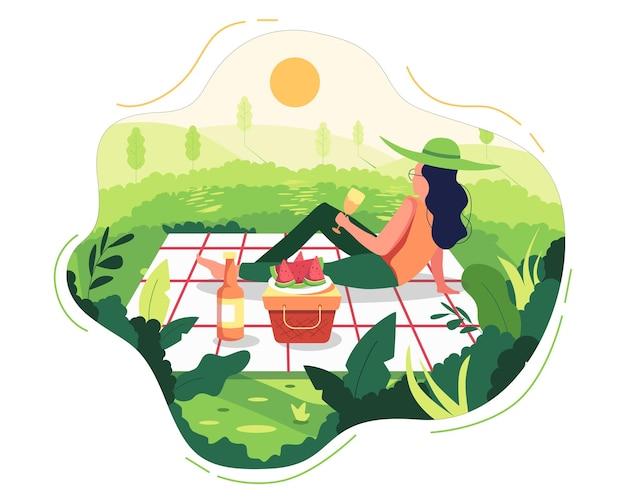 布の上に公園でピクニックの女性とピクニックバスケットを置きました。
