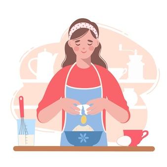 エプロンを着た女性が台所で生地をこねながら料理をしている。彼女は卵を持っています。