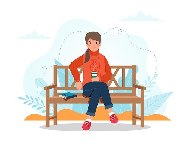コーヒーカップとベンチに座っている秋の女性