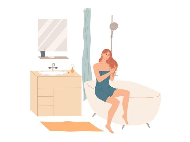 Женщина в банном полотенце наносит кондиционер для волос в ванной после душа дома. уход за волосами.