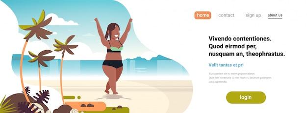 夏の休暇の概念の手を上げる海ビーチ熱帯の島の女の子にビキニ立っている女性