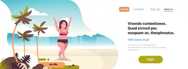 手を上げる海ビーチ熱帯の島の女の子にビキニ立っている女性
