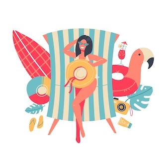 Женщина в бикини загорает, лежа на пляже