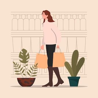 가게 앞의 여성은 식료품 그림의 일부 가방을 제공합니다