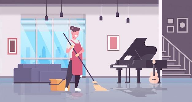 手袋とモップ主婦を使用して床のエプロン洗浄床の女の子の女性が家事のコンセプトのモダンなリビングルームのインテリアのクリーニングを行う