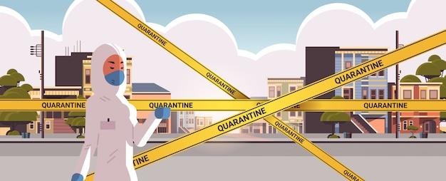 空の街の通りコロナウイルス感染武漢2019-ncovのパンデミックの健康リスクの概念の肖像水平に黄色の警告テープに危険のスーツの女性mers-cov検疫注意