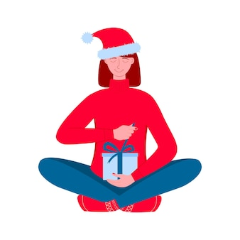Женщина в шляпе санты держит подарочную коробку и открывает ее, распаковывая подарок на рождественские каникулы