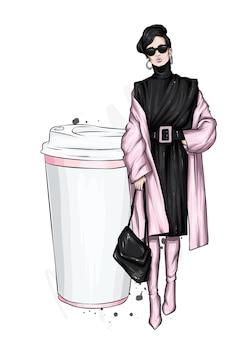 세련 된 코트와 커피 잔에 여자