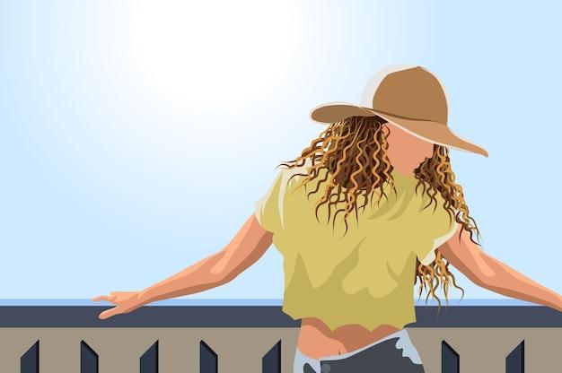 Женщина в шляпе от солнца желтой обрезанной футболке и джинсах позирует на балконе