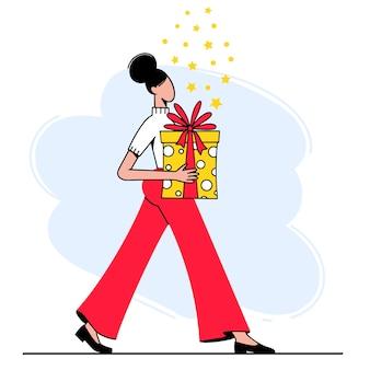 Женщина несет большую подарочную коробку.