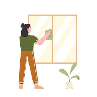 女性は家の窓を掃除しています