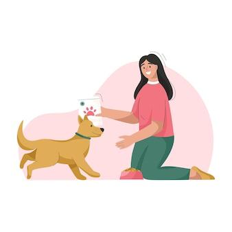 여자는 강아지를 돌보는 개 주인을 먹이