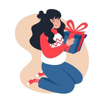 여자는 그녀의 손에 크리스마스 선물을 들고있다